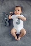 Nouveau-né à trois mois se trouvant sur le lit avec le numéro trois Photo libre de droits
