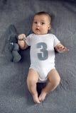 Nouveau-né à trois mois se trouvant sur le lit avec le numéro trois Image stock