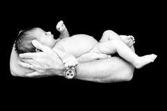 Nouveau-né dans le papa \ des 'mains de s Photos stock