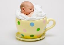 Nouveau-né dans une cuvette repérée jaune Photos stock