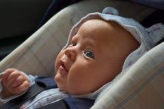 Nouveau-né heureux dans le siège de véhicule Photos libres de droits