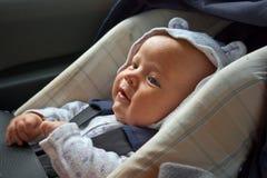 Nouveau-né heureux dans le siège de véhicule Photos stock