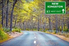 NOUVEAU panneau routier de KINGSTON contre le ciel bleu clair photographie stock