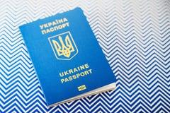 Nouveau passeport biométrique international bleu ukrainien avec la puce d'identification sur le fond blanc et bleu avec l'espace  Image libre de droits