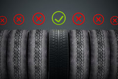 Nouveau pneu de voiture avec le coche vert se tenant parmi de vieux pneus Photographie stock libre de droits