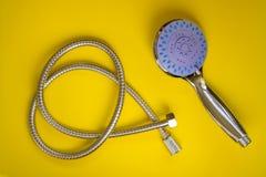 Nouveau pommeau de douche et tuyau flexible sur un fond jaune Pommeau de douche tenu dans la main avec avec le commutateur de fon photos stock
