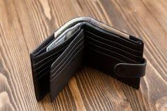 Nouveau portefeuille en cuir noir au-dessus de fond en bois foncé Photographie stock