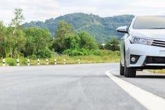 Nouveau stationnement argenté de voiture sur la route goudronnée Photo stock