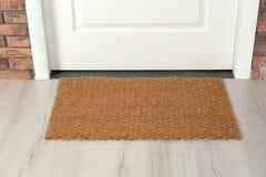 Nouveau tapis près de porte d'entrée Article de ménage photographie stock