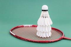 Nouveau volant du badminton trois avec des raquettes sur la cour verte de tapis Image libre de droits