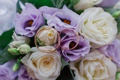 Nouveaux anneaux les épousant à côté du bouquet de la jeune mariée images libres de droits