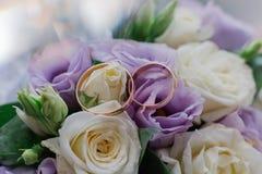 Nouveaux anneaux les épousant à côté du bouquet de la jeune mariée photos libres de droits