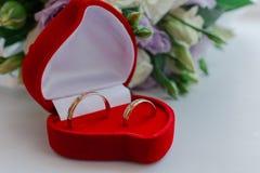 Nouveaux anneaux les épousant dans une boîte rouge à côté du bouquet de la jeune mariée photographie stock libre de droits