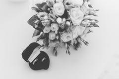 Nouveaux anneaux les épousant dans une boîte rouge à côté du bouquet de la jeune mariée images stock