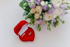 Nouveaux anneaux les épousant dans une boîte rouge à côté du bouquet de la jeune mariée photo libre de droits
