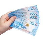 Nouveaux billets de banque russes dénommés en 2000 roubles dans une main masculine d'isolement sur un blanc Images libres de droits