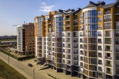 Nouveaux immeubles grands et voitures et maisons garées de banlieue sur le fond de l'espace de copie de ciel bleu photos libres de droits