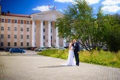 Nouveaux mariés à l'arrière-plan d'un bâtiment Images stock