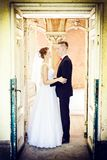 Nouveaux mariés étreignant à la porte dans une vieille maison Photographie stock libre de droits