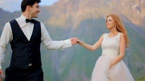 Nouveaux mariés affectueux marchant dans un pré contre le contexte de belles montagnes banque de vidéos