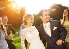 Nouveaux mariés avec l'invité sur leur réception en plein air Photo stock