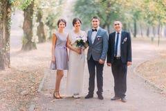Nouveaux mariés avec le garçon d'honneur et la demoiselle d'honneur posant à la ruelle ensoleillée de parc Photo stock