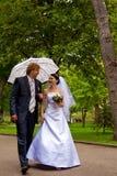 Nouveaux mariés avec le parapluie Photographie stock libre de droits