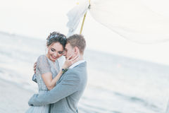 Nouveaux mariés avec plaisir caressant au bord de la mer Photo stock