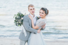 Nouveaux mariés avec plaisir caressant au bord de la mer Image stock