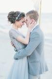 Nouveaux mariés avec plaisir caressant au bord de la mer Photographie stock libre de droits
