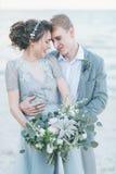 Nouveaux mariés avec plaisir caressant au bord de la mer Photographie stock