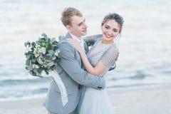 Nouveaux mariés avec plaisir caressant au bord de la mer Image libre de droits