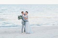 Nouveaux mariés avec plaisir caressant au bord de la mer Images stock