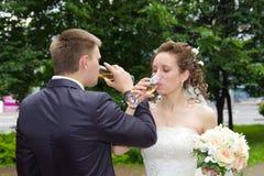 Nouveaux mariés buvant du champagne Photo stock