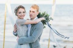 Nouveaux mariés caressant au bord de la mer Photo stock