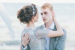 Nouveaux mariés caressant au bord de la mer Image stock