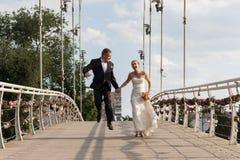 Nouveaux mariés courant sur le pont Photo libre de droits