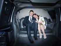Nouveaux mariés dans la limousine image stock