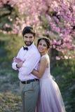 Nouveaux mariés dans le support d'amour sur la nature, dans la perspective des enjeux en bois, par temps ensoleillé Le marié élég image stock