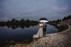 Nouveaux mariés de couples avec le grand parapluie Photo stock
