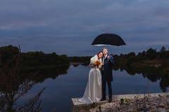 Nouveaux mariés de couples avec le grand parapluie Photos libres de droits