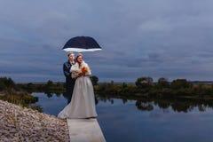 Nouveaux mariés de couples avec le grand parapluie Image stock
