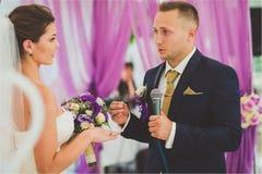 Nouveaux mariés de sourire heureux élégants sur la cérémonie de mariage extérieure de luxe dans la tente de brume près de l'océan Images stock