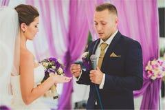 Nouveaux mariés de sourire heureux élégants sur la cérémonie de mariage extérieure de luxe dans la tente de brume près de l'océan Photo stock