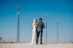Nouveaux mariés embrassant passionément tout en se tenant sur la route Photo stock