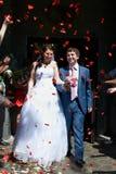 Nouveaux mariés et pétales heureux de rouge de vol Photo libre de droits