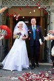 Nouveaux mariés et pétales heureux de rouge de vol Photos libres de droits