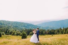 Nouveaux mariés gais buvant du vin dehors, célébrant leur mariage Ciel ensoleillé de Forest Hills et d'espace libre comme fond Photo libre de droits