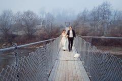 Nouveaux mariés gais marchant et riant sur le pont en bois Lune de miel aux montagnes Photos stock