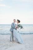 Nouveaux mariés heureux ayant l'amusement par la mer Images stock